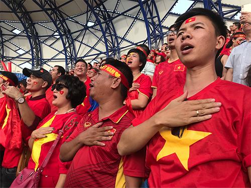Các cầu thủ và người hâm mộ của đội tuyển Việt Nam trong nghi thức hát quốc ca. Ảnh: Vietravel.