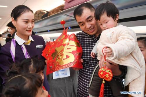Tiếp viên đường sắt Liu Lu tặng quà cho khách. Ảnh:Zhang Duan/Xinhua.