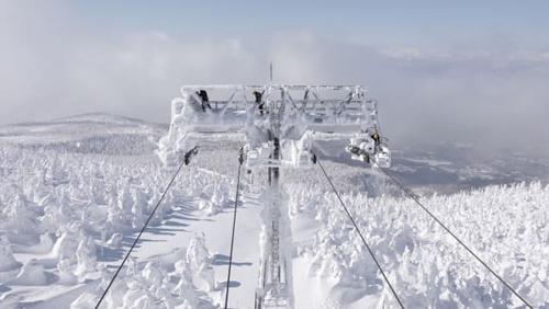 Cảnh nhìn ra từ trung tâm quan sát, trong đó là những người đang dọn tuyết khỏi đỉnh tháp cáp treo.