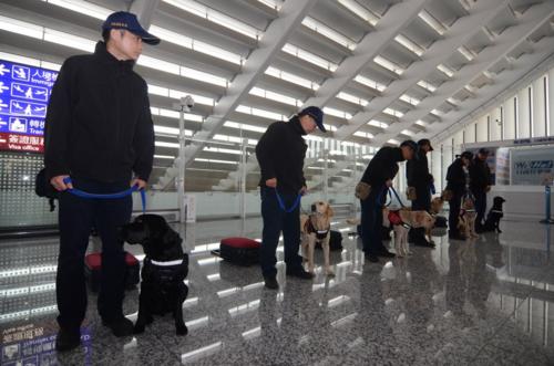 Các sĩ quan cùng chó nghiệp vụ làm nhiệm vụ tại sân bay quốc tế Đào Viên. Ảnh:Central News Agency.