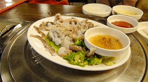 Bạch tuộc sống ăn kèm theo nước chấm gồm dầu mè, tương ớt, giấm và đường để thực khách tùy ý pha chế theo khẩu vị. Ảnh:Giphy.