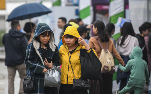 Khách tham quan hội chợ trong thời tiết mưa lạnh.
