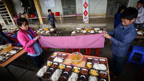Bữa cơm trưa trên sân trường của học sinh ở Chiến Phố. Ảnh: Đinh Tùng.