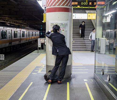 Một người đàn ông đứng ngủ tại ga tàu điện ngầm Tokyo. Ảnh: Magnus Wennman.