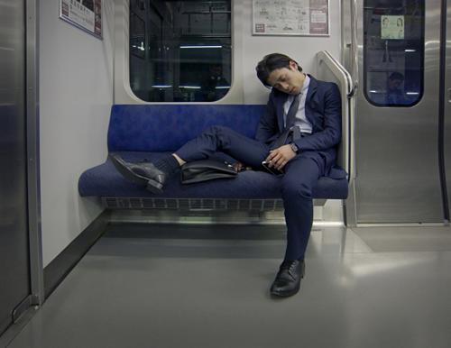 Nhân viên văn phòng ngủ gục trên tàu điện. Ảnh:Tokyo Form/Flickr.