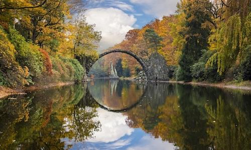 Cầu Rakotzbrücke giữa rừng lá đổ sắc vàng, đỏ vào mùa thu.