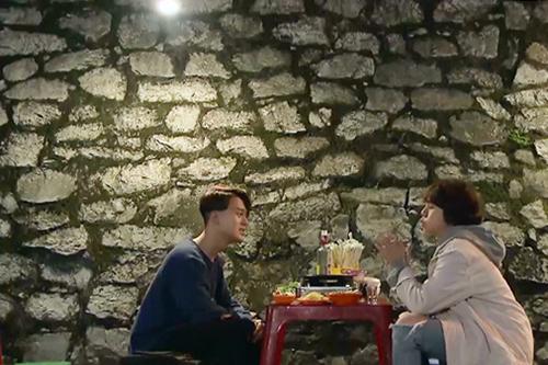 Bức tường đá quen thuộc ở quán Vân, nơi Dương và Vân ngồi thưởng thức món ăn trong cảnh phim ở tập 25. Ảnh chụp màn hình.