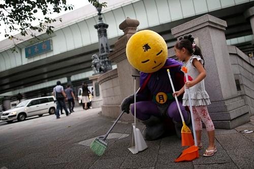 Siêu anh hùng chống xả rác Mangetsu-man tuần tra trên đường phố Tokyo và nhắc nhở các bạn nhỏ giữ vệ sinh chung. Ảnh: Issei Kato/Reuters.