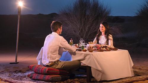 Du khách thưởng thức bữa tối trên sa mạc, dịch vụ này do một resort 5 sao ở Dubai cung cấp. Ảnh: National.