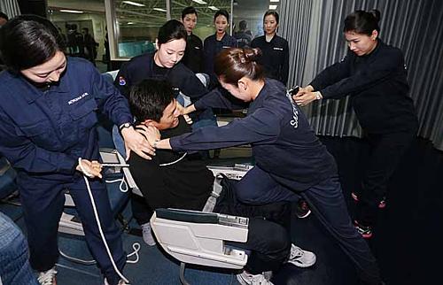 Trong trường hợp xấu nhất, tiếp viên hoàn toàn có quyền còng tay những hành khách quá khích trên chuyến bay. Ảnh: Korea Joongang.
