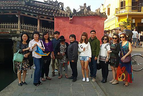 Chị Thư (cầm cờ) và đoàn du khách bị kẹt lại tại Đà Nẵng sau sự cố. Trong ảnh, đoàn chụp ảnh tại Chùa Cầu,Hội An.