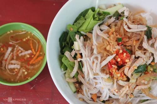 Bún bìQuán Tư Loan là địa chỉ không chỉ có tiếng ở chợ Bàn Cờ mà còn cả ở Sài Gòn với đặc sản miền Tây, bùn bì. Món ănbao gồm sợi bún tươi ăn kèm giá, rau sống và không thể thiếu thành phần quan trọng: lớp bì heo. Bì có độ dai, vị bùi và thơm thoảng mùi thính gạo. Món ăn có thêm rau sống bên dưới khiến bạn ăn ngon miệng mà không bị ngán. Quán có không gian khiêm tốn, bán từ 11h đến 17h mỗi ngày.Giá một tô bún bì dao động từ 25.000 - 35.000 đồng. Ngoài bún bì, quáncòn có thêm món bún thịt nướng, bún chả giò. Ảnh: Thư Kỳ.