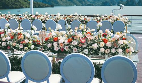Một đám cưới quy mô nhỏ khoảng 70 người trên du thuyền Paradise Elegance với tông màu chủ đạo cam san hô đến từ 7799 Wedding Storyteller.