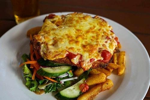 Gà parmigiana xuất hiện lần đầu tiên năm 1980 ở Australiavà trở thành món ăn biểu tượng của quốc gia này. Ban đầu món ăn được nấu với nguyên liệu chính là cà tím, sau đó đã phát triển thành gà hầm sốt cà chua với phô mai và giăm bông prosciutto. Món ăn này thường được phục vụ chung với khoai tây chiên trong các quán rượu với giá bán là 6 AUD (khoảng 94.000 đồng). Ảnh: Irymple Hotel.