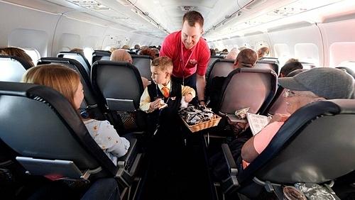 Tiếp viên hàng không danh dự S.J. phát đồ ăn cho hành khách trên máy bay. Ảnh: Sonya Padgett.