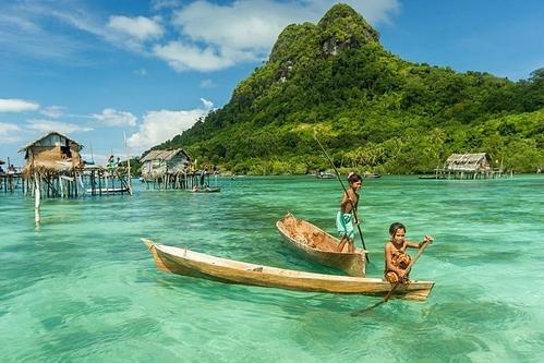 Những đứa trẻ địa phương bơi thuyền ở đảo. Ảnh: Shutterstock/Yusnizam Yusof.