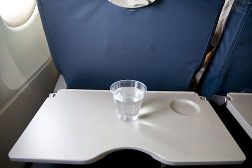 Vì sao chỗ để cốc trên bàn ăn máy bay quá nông?
