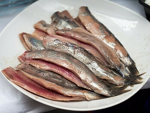Cá trích thường được ăn kèm với hành tây và dưa chua. Ảnh: Takeaway/WikiCommons.