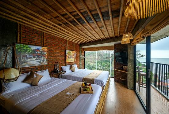 Phòng nghỉ hai giường ngủ với tông màu vàng chủ đạo, gường tre, trần tre nứa và sàn gỗ tạo cảm giác gần gũi với thiên nhiên.