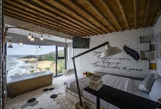 Một căn phòng nhìn ra biển dành cho du khách yêu thích phong cách tối giản. Phòng có màu trắng chủ đạo, nội thất màu đen, xám.