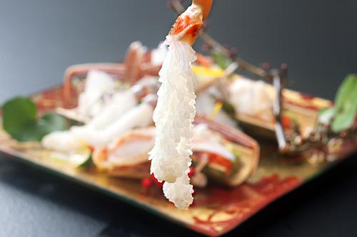 Đầu bếp làm sashimi cua tuyết bằng cách lột bỏ lớp vỏ chân rồi ngâm phần thịt vào nước đá 10 phút. Thịtcua xòe ra trông như chùm lá thông. Khi ăn thực khách có thể chấm với tương và thưởng thức vị ngon ngọt nguyên bản của thịt cua. Ảnh: Guide Michelin.