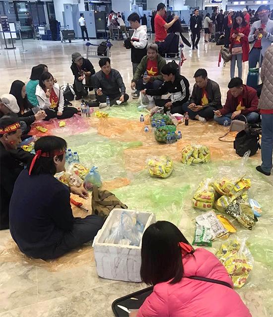 Một nhóm CĐV mang theo đồ ăn tới sân bay chờ giờ khởi hành về Việt Nam. Ảnh: Son Trinh.