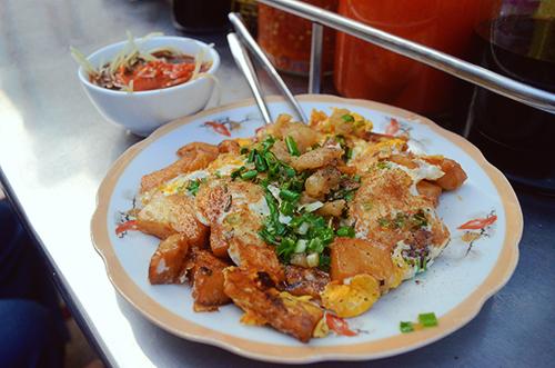 Bột chiênBắt nguồn từ món ăn của người Tiều, Trung Quốc, bột chiên đã trở thành món ăn vặt yêu thích của người dân Sài Gòn. Món ăn được làm bột gạo, trứng, hành lá và tóp mỡ. Bột thường được chiên trên chiếc chảo lớn, để ngoài mặt giòn nhưng vẫn giữ độ mềm bên trong. Khi thưởng thức, bột chiên bùi ngậy và dễ ăn, bạn có thể cho thêm nước tương, ăn kèm gỏi đu đủ.Bột chiên được bán với giá khoảng 20.000 - 30.000 đồng một suất. Địa chỉ gợi ý cho món ăn này là quán Kim Ngọc, đường Nguyễn Thiện Thuật và quán Đạt Tần trên đường Võ Văn Thành. Ảnh: Phong Vinh.