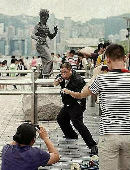Một người đàn ông đang bắt chước bức tượng của huyền thoại võ thuật Lý Tiểu Long trên Đại lộ Ngôi sao của Hong Kong. Ảnh: Stuart Heaver/SCMP