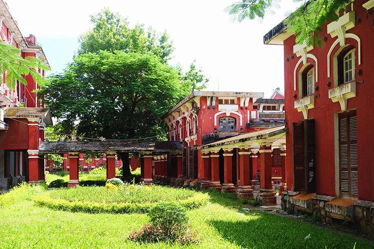 Khoảng đất trống giữa các khu nhà được phủ xanh bởi thảm cỏ và cây cao, tạo không gian dịu mát trong ngôi trường màu đỏ. Ảnh: Nguyễn Hoàng Hà