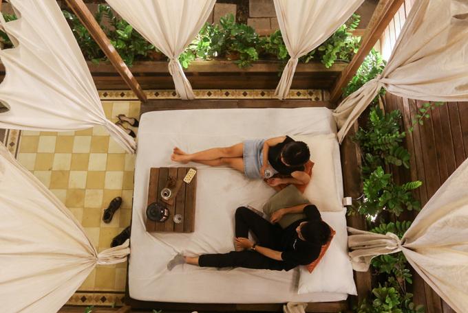 Bạn có thể uống nước thư giãn tại quán cà phê lều trong hẻm đường Nguyễn Văn Đậu (quận Bình Thạnh). Nơi khách ngồi là những ô lều được trải đệm và gối có thể nằm thoải mái,lắp rèm bao quanh tuy nhiên không thể kéo kín. Khuôn viên quán rộng rãi, có không gian mở, nhiều cây xanh và hồ bơi tạo sự mát mẻ. Quán mở cửa từ 7h đến 20h. Thức uống có giá trong khoảng 35.000 - 140.000 đồng và được đựng trên khay gỗ đặt lên đệm. Ảnh: Quỳnh Trần