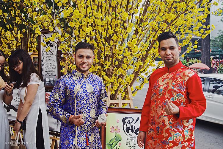 Rajesh (trái) và bạn mặc áo dài đi dạo phố hoa ở Nhà Văn hóa Thanh niên.
