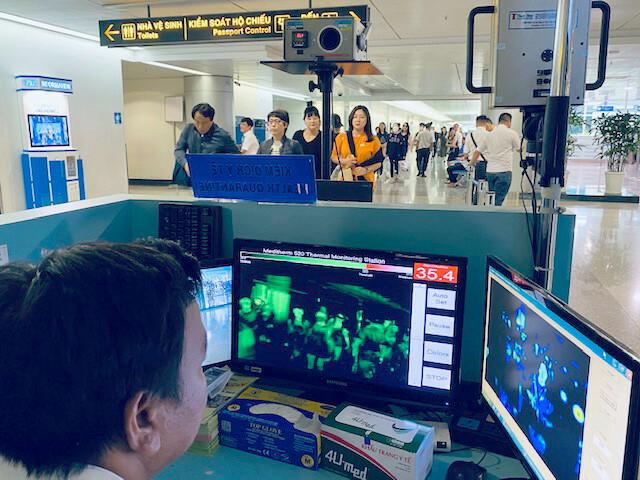 Kiểm tra thân nhiệt hành khách nhập cảnh qua sân bay quốc tế Tân Sơn Nhất. Ảnh: Duy Tính.