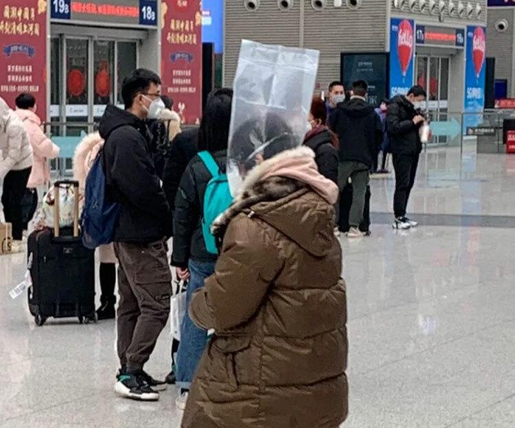 Một người phụ nữ đội túi giấy bóng lên đầu. Tại Trung Quốc, hành khách sẽ bị cấm sử dụng phương tiện giao thông công cộng nếu họ không đeo khẩu trang.