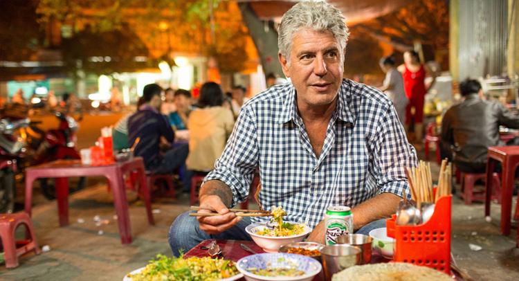 Cơm hến còn là đặc sản hấp dẫn nhiều du khách nước ngoài. Trong show ẩm thực Parts Unknown chiếu trên kênh CNN năm 2014, cố đầu bếp Anthony Bourdain đã rất thích thú khi có dịp thưởng thức cơm hến trên vỉa hè. Ảnh: CNN.