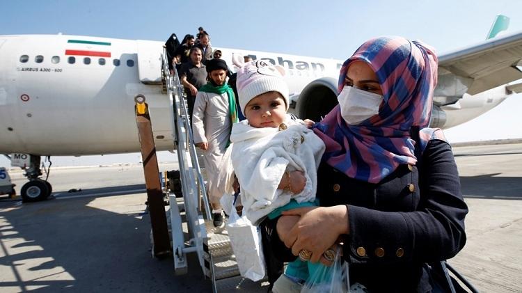 Hành khách đeo khẩu trang rời khỏi máy bay khi đến sân bay Najaf, Iraq. Ảnh: Alaa al-Mar/Reuters.