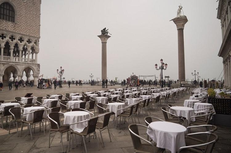 Bàn ghế của nhà hàng trống không trên Quảng trường Thánh Mark ở Venice. Vốn là một trong những thành phố điển hình cho tình trạng quá tải du lịch, Venice nay trống không. Điều khiến thành phố kênh đào này khác biệt với những điểm du lịch khác như Rome và Milan, là người dân gần như không có nguồn thu nhập nào khác ngoài du lịch. Ảnh: Renata Brito/AP.