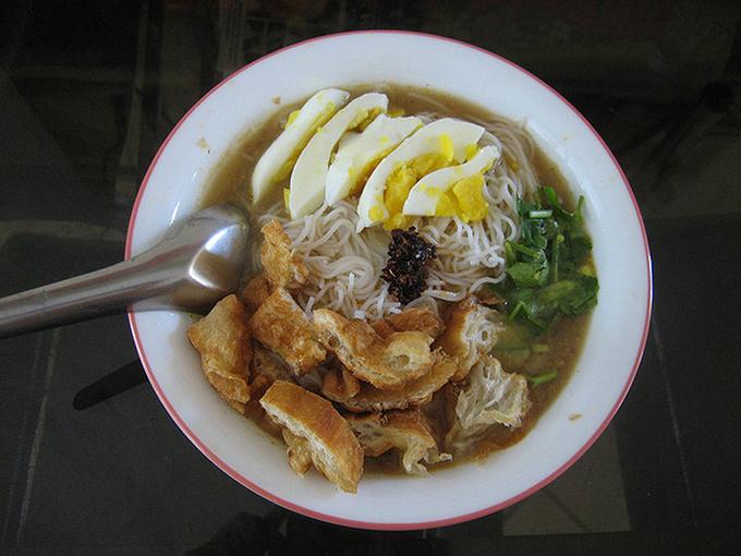 Bún gồm một quả trứng luộc thái lát và akyaw (rau chiên giòn) cùng một đĩa bột đậu lăng. Ảnh:Saveur.