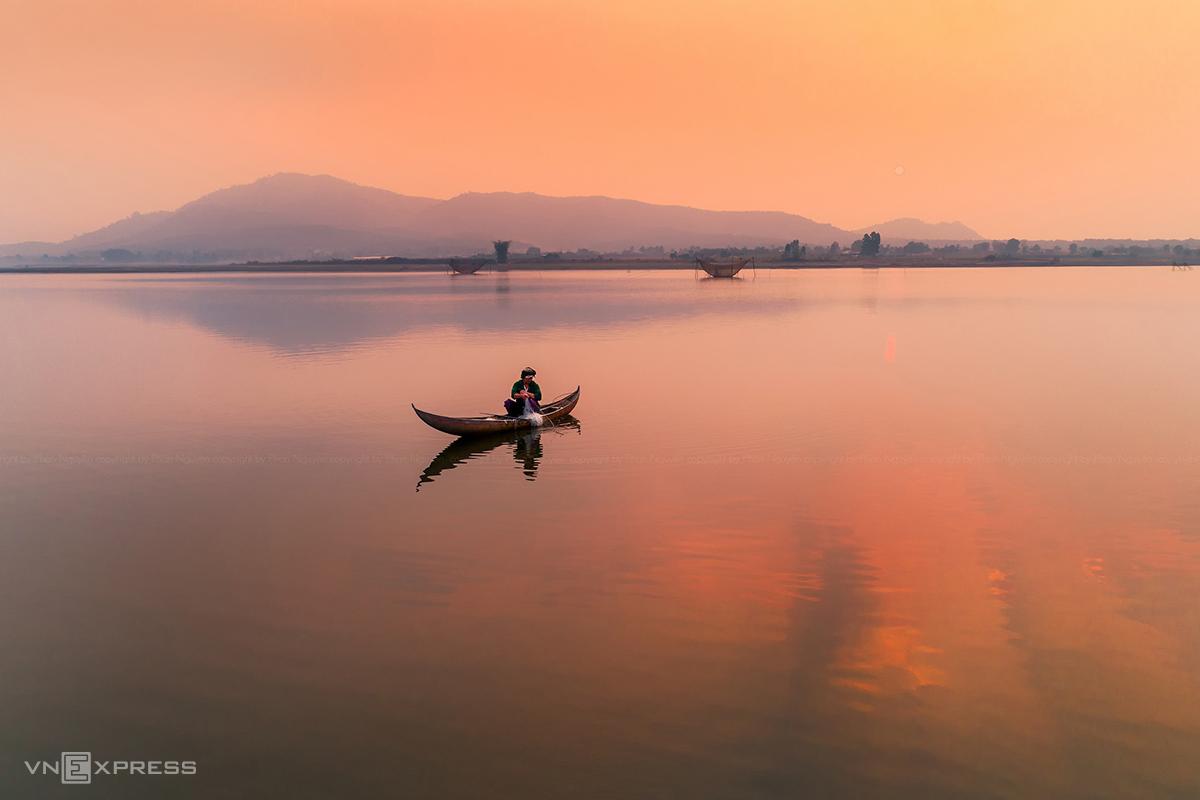 Ngư dân thả lưới trên hồ lúc bình minh. Ảnh: Phan Nguyên.