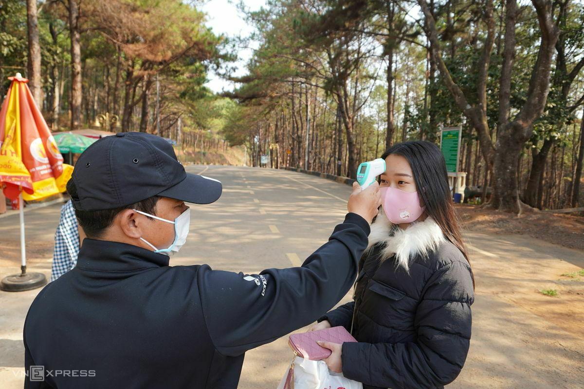 Rơ Châm Kát, nhân viên kiểm soát vé ở Biển Hồ đo thân nhiệt cho từng khách tham quan. Ảnh: Trần Hóa.