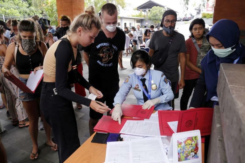 Cảnh sát xuất nhập cảnh hướng dẫn người nước ngoài thực hiện thủ tục xin gia hạn visa tại Bali ngày 23/3. Ảnh: Johannes P. Christo/Reuters.