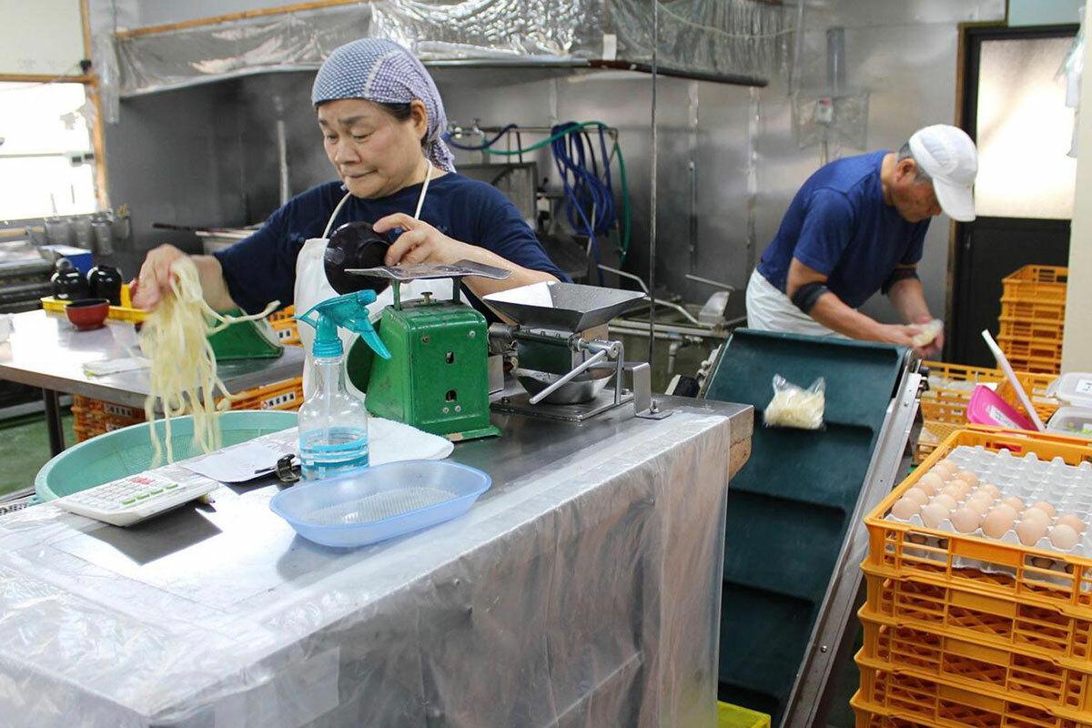 [Với các đơn đặt hàng dày đặc của siêu thị, chủ cửa hàng, ông Youichi Matsuka luôn bận rộn chế biến mì, còn vợ ông, bà Keiko, cân và chia mì vào hàng trăm gói nhỏ. Taichi, con trai của họ có nhiệm vụ làm bột, vớt mì vừa luộc nóng sang phần làm mát và cũng hỗ trợ cân và đóng gói để giao hàng. Ảnh: BBC.