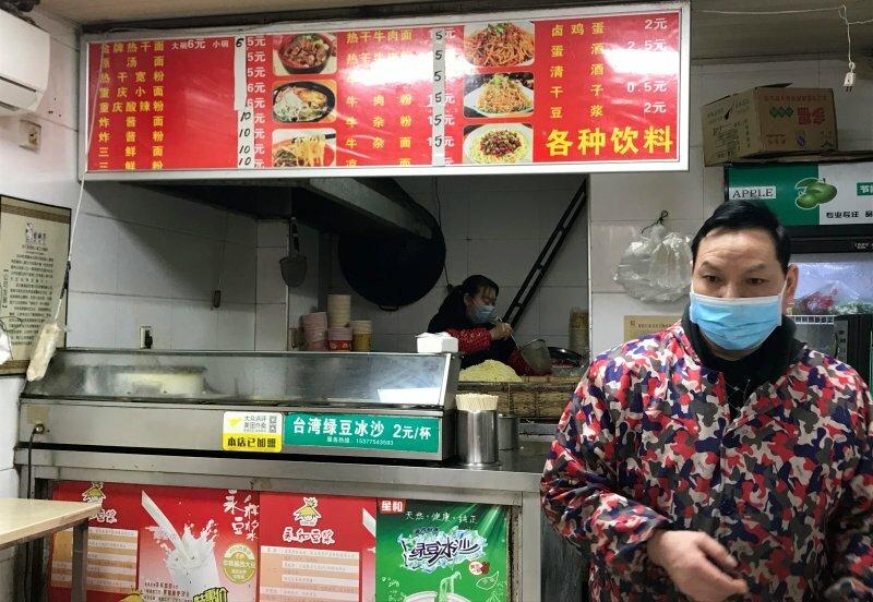 Hai vợ chồng chủ quán mỳ đang chuẩn bị đồ để khách mua về tại Vũ Hán ngày 31/3. Ảnh: Time.