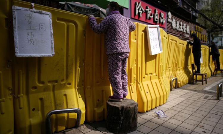 Người dân Vũ Hán đứng lên ghế để mua đồ qua hàng rào phong tỏa ngày 1/4. Ảnh: Reuters.