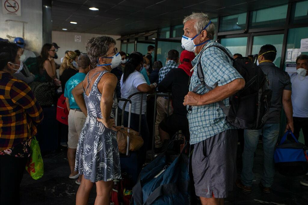 Du khách chờ đợi tại sân bay quốc tế La Aurora ở Guatemala vào ngày 24/ 3 trong một chuyến bay thuê bao được điều phối bởi Đại sứ quán Mỹ. Ảnh: Moise Castillo/AP.